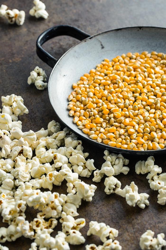 bowl of popcorn kernels next to popcorn