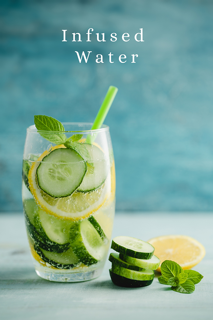 glass with water, lemons, and cucumber