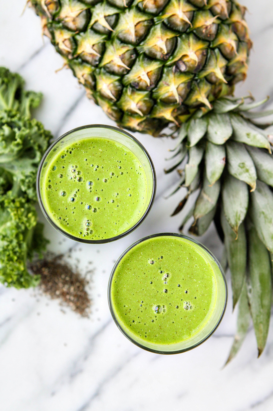 green smoothie in a glass with pineapple and kale