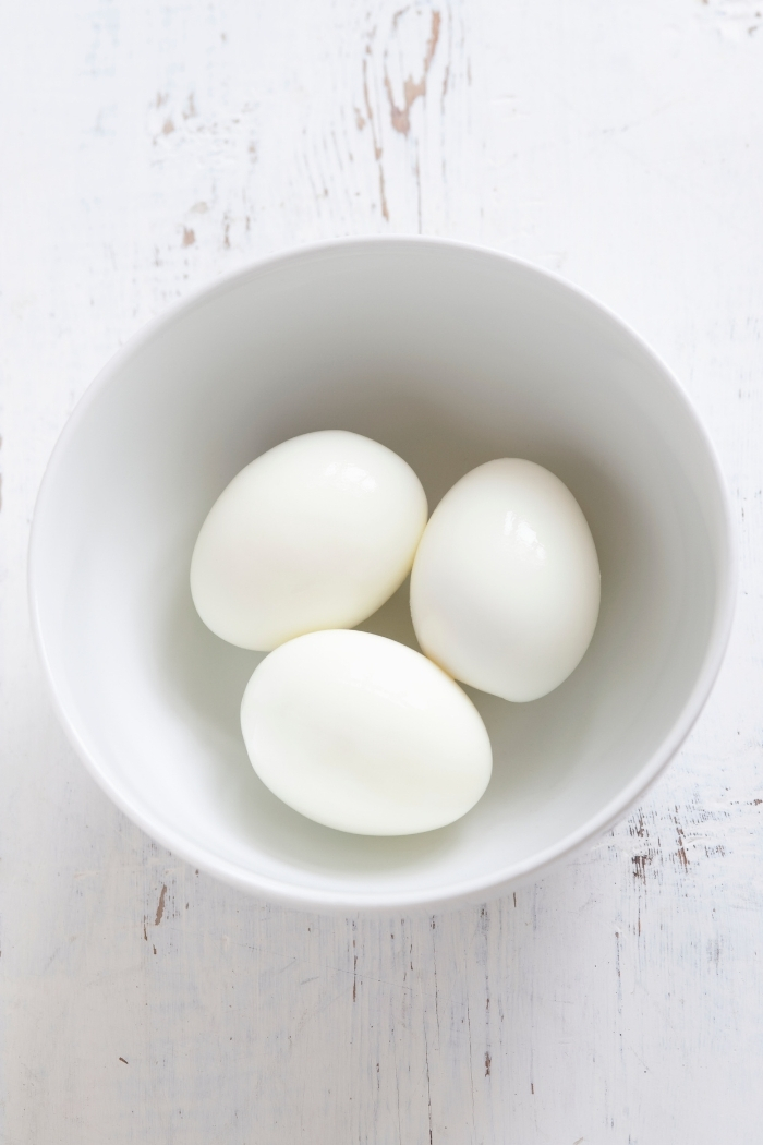 white bowl with peeled hard boiled eggs on a white wooden background