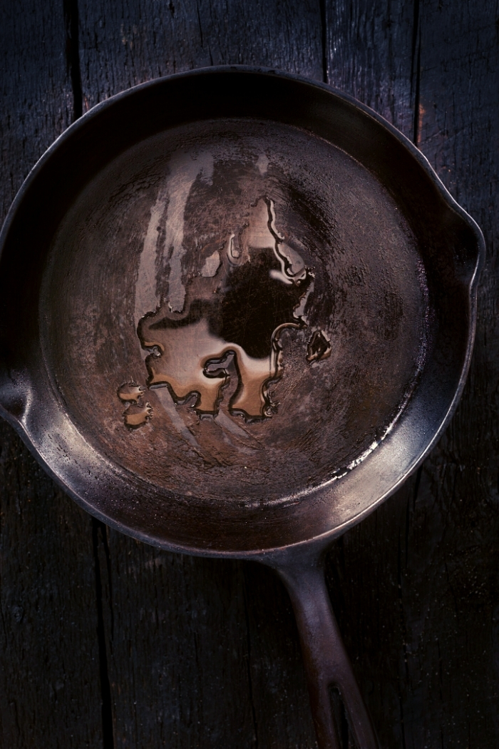 overhead shot of a cast iron skillet with oil in it on a dark background