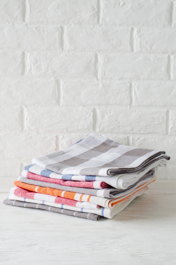 a stack of folded dish towels on a white background
