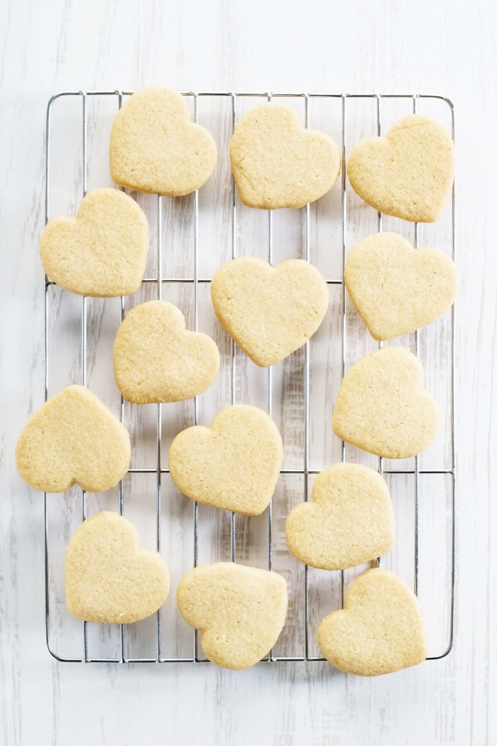 wire rack with heart shaped cut out cookies on a white background