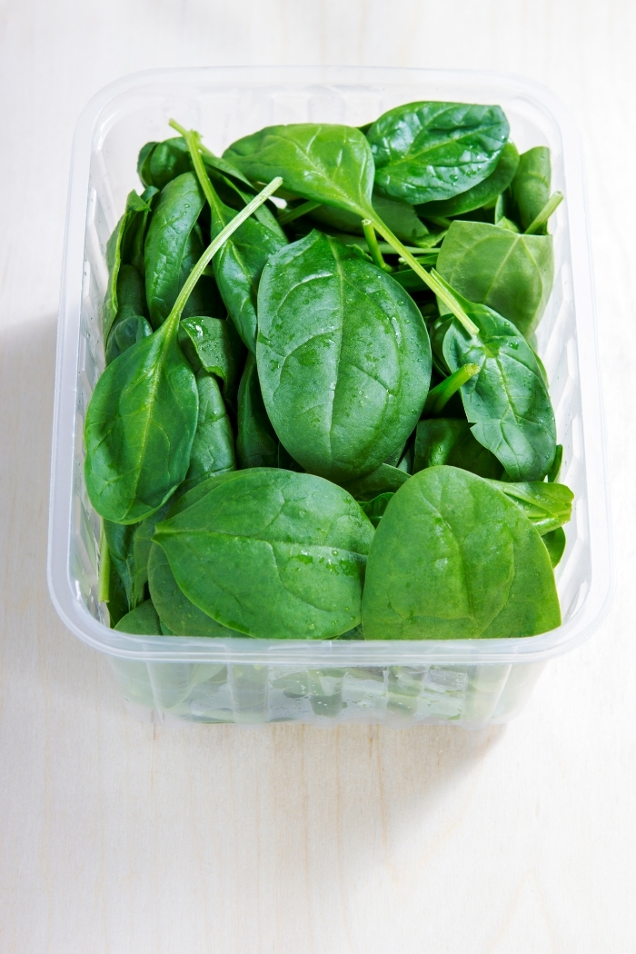plastic container with baby spinach leaves