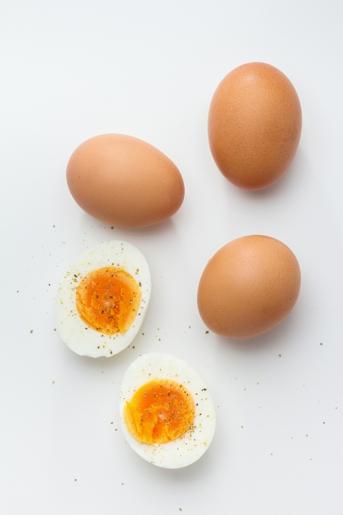 white background with brown eggs and a hard boiled egg