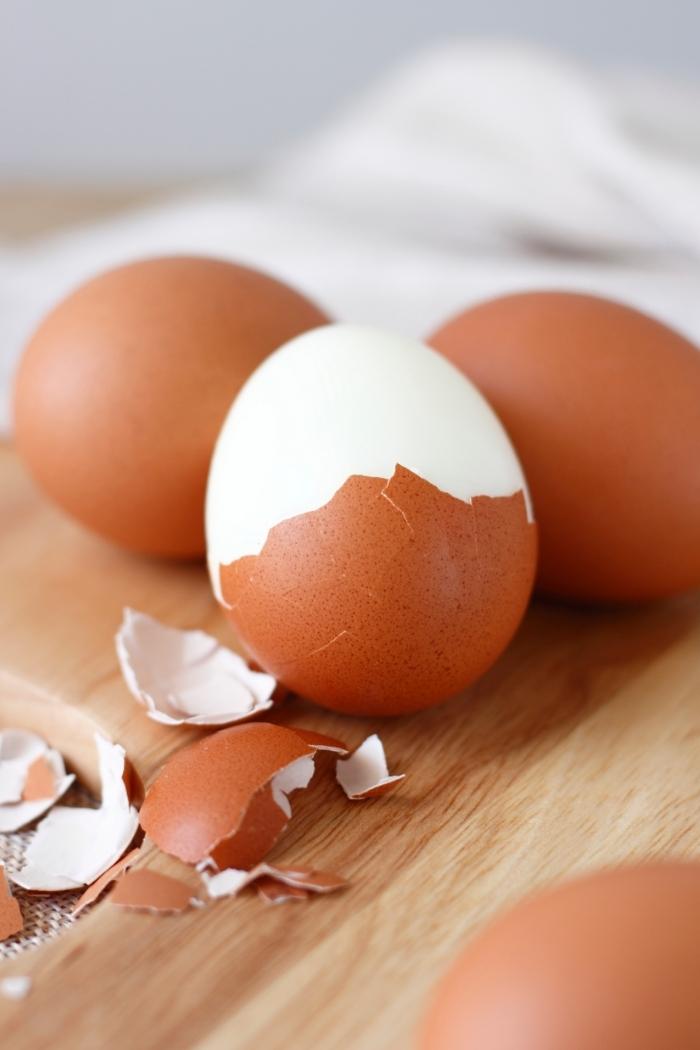 brown hard boiled eggs being peeled