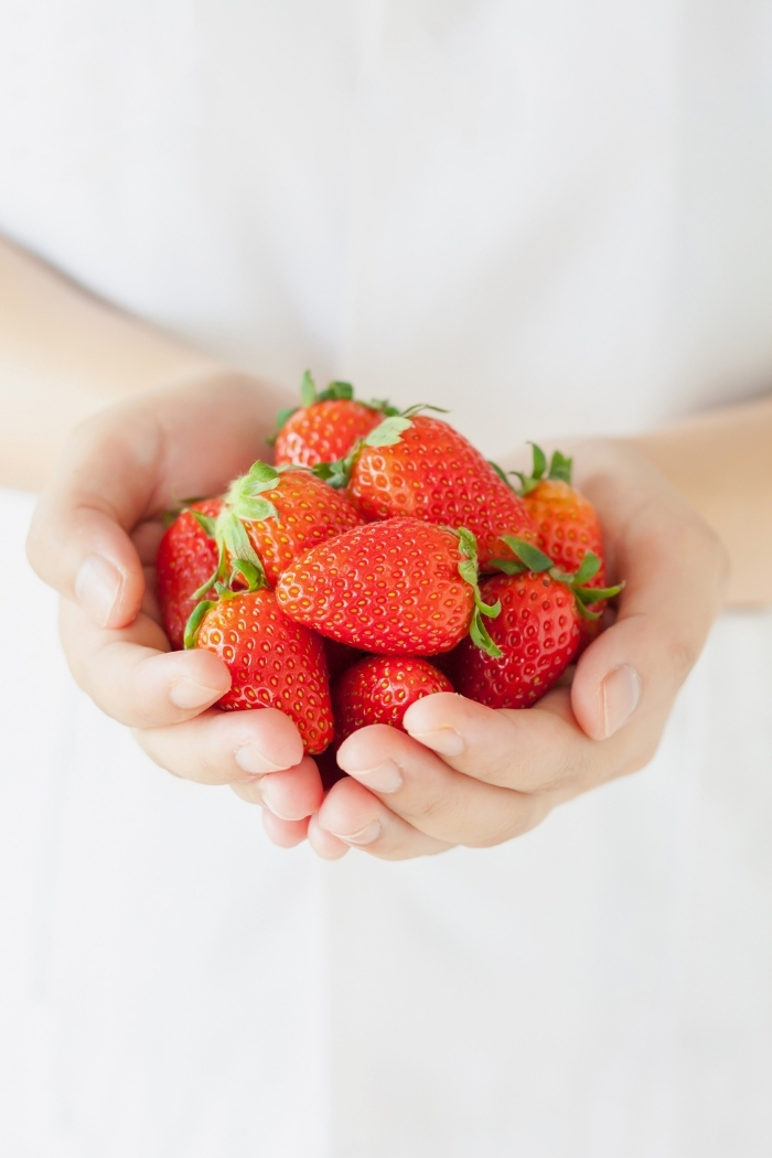 child holding fresh strawberries in hands