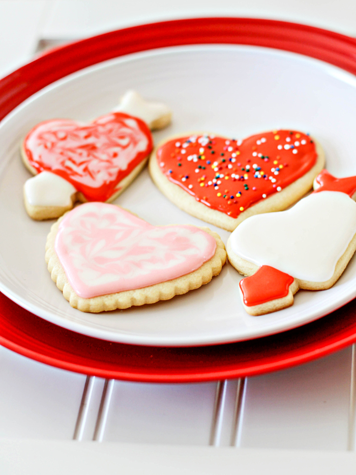 cut out sugar cookies decorated for valentine's day on white plate
