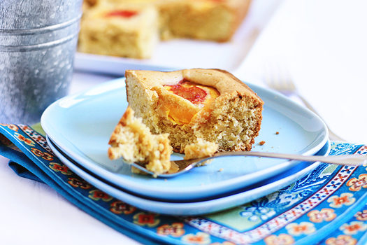 close up of a slice of peach cake on a blue plate with a fork