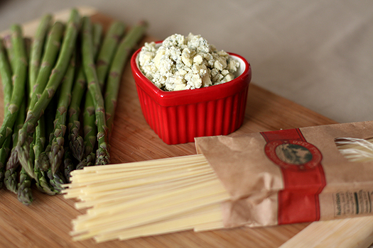 Ingredients needed to make gorgonzola pasta sauce on a wood cutting board.
