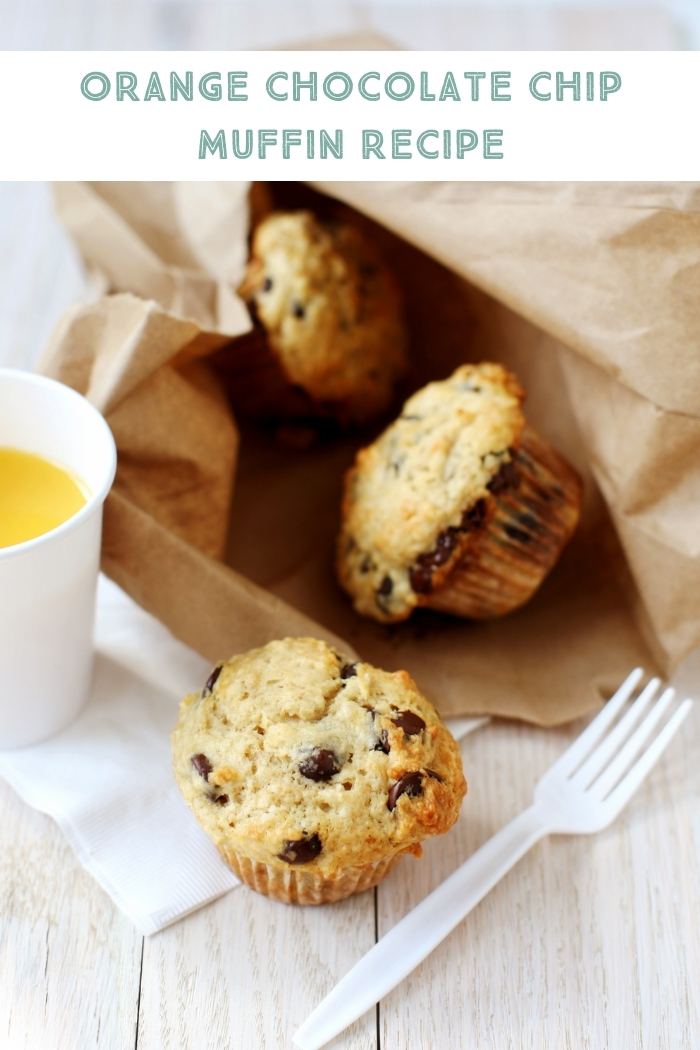 orange chocolate chip muffins in a brown paper bag on a table